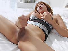 Big boobs shemale strokes her dick while lying in bed